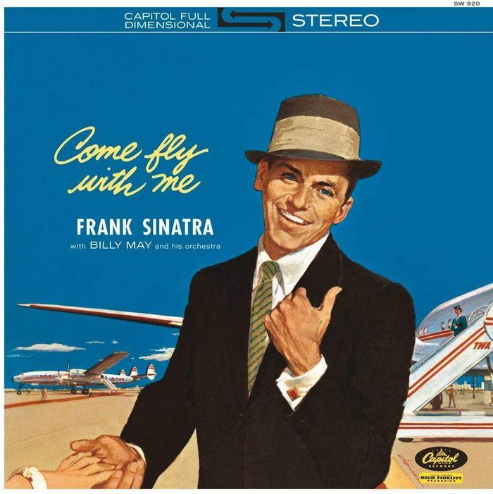 """Parte frontal do álbum """"Come Fly With Me"""" de Frank Sinatra. É possível notar ao fundo do cantor que há a presença de 2 aeronaves do tipo Lockheed Super Constellation da extinta companhia aérea TWA; tais aeronaves eram utilizadas para voos transatlânticos à época."""